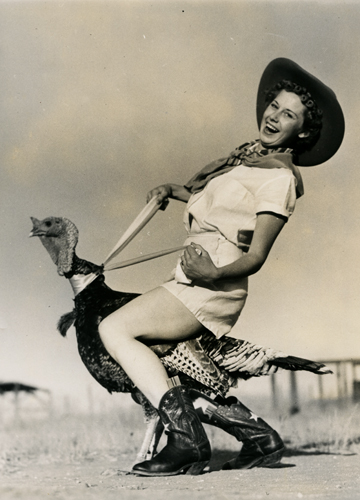 Old time photo of a cowgirl riding a turkey