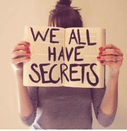 "photo of woman holding sign ""we all have secrets"""
