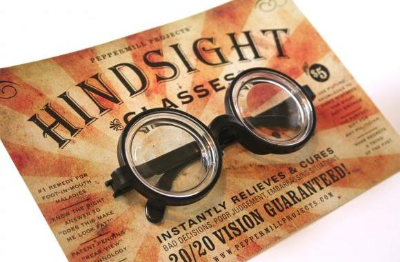 "glasses sitting on a flier that says ""hindsight"""