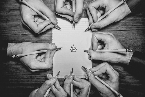 black and white photo of many hands writing on one piece of paper