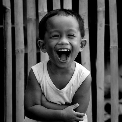 black and white photo of little boy laughing