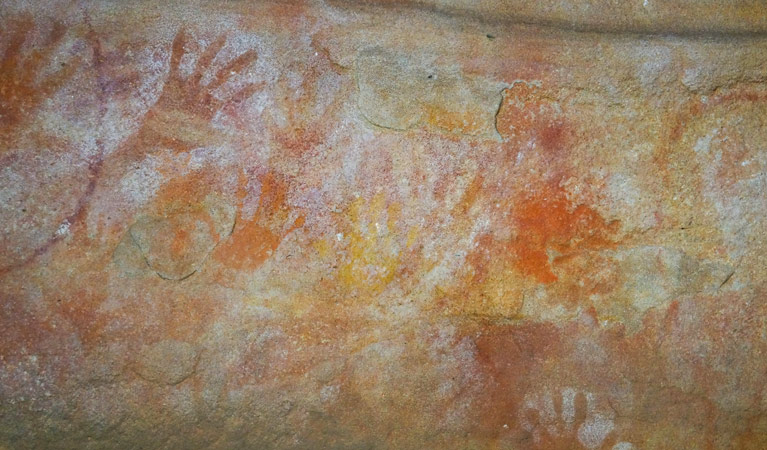 photo of red handprint in cave